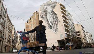 Un immigrato che vive in Grecia, spinge un carrello della spesa pieno di spazzatura, davanti a un murale dipinto su un edificio. John Kolesidis